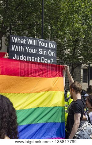 London England - June 25 2016: A religious fanatic is being covered by a rainbow flag on the Gay Pride's march day in London England on the 25th of June 2016.
