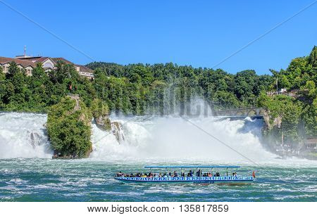 Neuhausen am Rheinfall, Switzerland - 22 June, 2016: people in a boat at the Rhine Falls. The Rhine Falls (German: Rheinfall) is the largest plain waterfall in Europe located on the Rhine river in Switzerland.