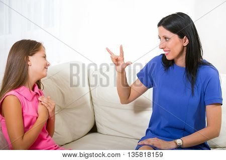 Smiling deaf girl learning sign language at home
