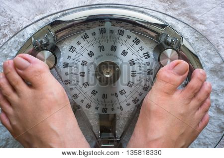 Photo showing two feet on a modern analog scale taking weight