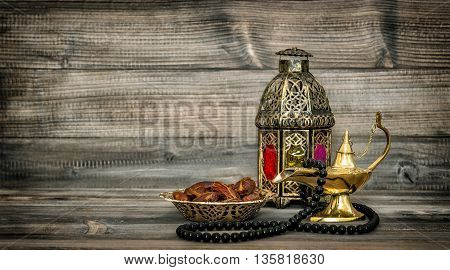 Arabic lantern and islamic rosary beads. Oriental holidays decoration with dates fruits. Vintage style toned picture
