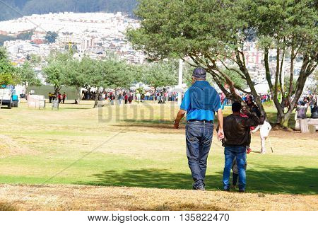 QUITO, ECUADOR - JULY 7, 2015: Men dressing with blue color walking to arrive to pope Francisco mass, at the end a lot of people.