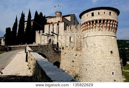 Brescia, Italy - May 30, 2006: A sloped roadway leads to the portcullis and entrance gate to the feudal era 1343 fortified Castello built by the Visconti family
