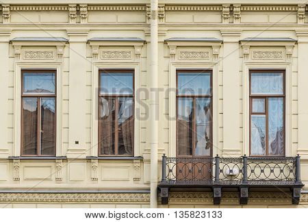 Several windows in a row and balcony on facade of urban office building front view St. Petersburg Russia