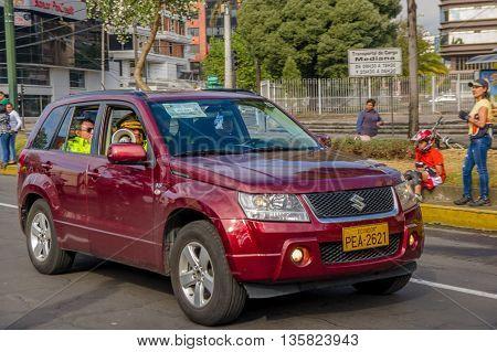 QUITO, ECUADOR - JULY 7, 2015: Police inside a wine color car, Suzuki big vitara. People outside,