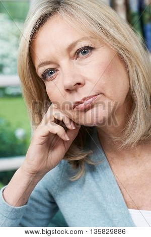 Head And Shoulders Portrait Of Thoughtful Mature Woman At Home