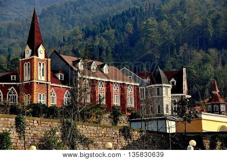 Bai Lu China - November 17 2013: Steepled tower and large meeting hall with gothic windows in the Sino-French village built following the 2008 earthquake