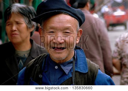 Ao Ping China - September 14 2006: Smiling elderly toothless Chinese man wearing a cap