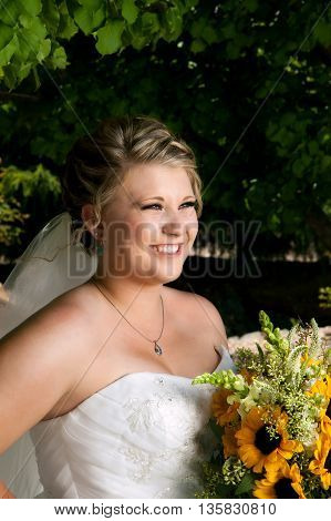 A beautiful bride smiles off into the distance. She is lit well with a dark lush background of tree leaves. She holds her sunflower bouquet.
