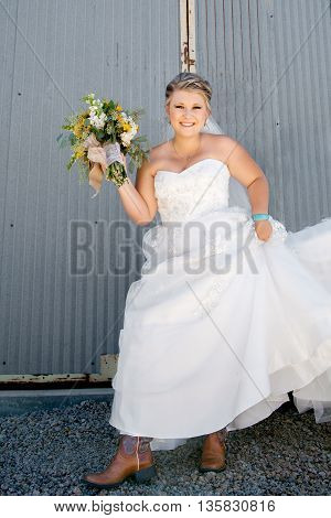 A beautiful country western bride shows off her cowgirl boots under her wedding dress.