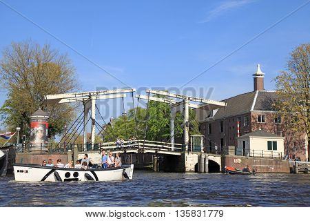 AMSTERDAM, NETHERLANDS - MAY 6, 2016: Cityscape with boats and drawbridge on a canal in Amsterdam, Netherlands