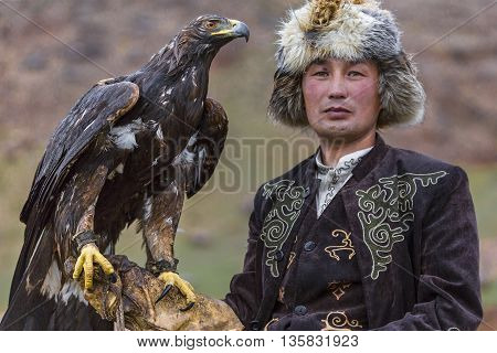 ISSYK KUL, KYRGYZSTAN - MAY 29, 2016: Kyrgyz hunter holds his golden eagle and looks at me.