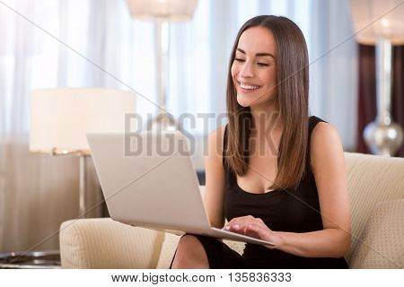 Working in a good mood. Contented pretty young woman working on her laptop while sitting on the couch in the hotel