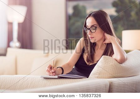 Calm time. Thoughtful relaxed adorable woman sitting on the sofa and writing in the notebook and touching a neck with her hand