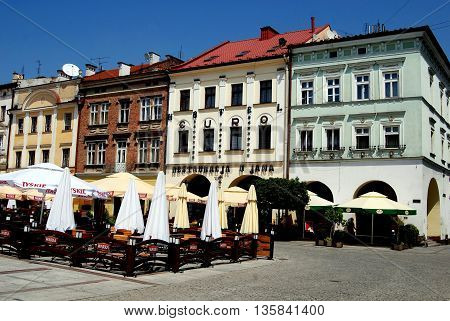 Tarnow Poland - June 12,  2010: Outdoor cafés and restaurants front the handsome Renaissance and Baroque buildings lining the Rynek Market Square