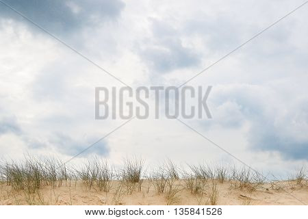 Cloudy sky above a dune rim with room for text