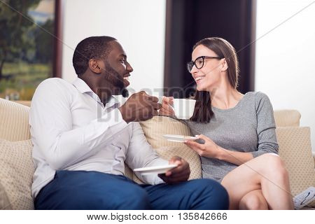 At last relaxation. Adorable young woman and bearded mature afro American man sitting on the sofa and drinking coffee after hard working day