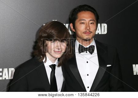 NEW YORK-OCT 9: Actors Chandler Riggs (L) and Steven Yeun attend AMC's 'The Walking Dead' season six premiere at Madison Square Garden on October 9, 2015 in New York City.
