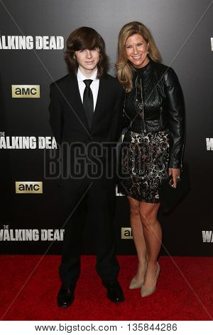 NEW YORK-OCT 9: Actors Chandler Riggs (L) and Gina Riggs attend AMC's 'The Walking Dead' season six premiere at Madison Square Garden on October 9, 2015 in New York City.