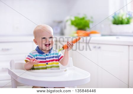 Happy baby sitting in high chair eating carrot in a white kitchen. Healthy nutrition for kids. Bio carrot as first solid food for infant. Children eat vegetables. Little boy biting raw vegetable.