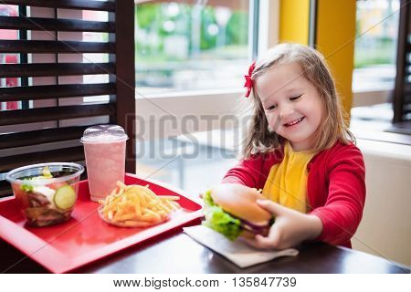 Little girl eating hamburger and French fries in a fast food restaurant. Child having sandwich and potato chips for lunch. Kids eat unhealthy fat food. Grilled fastfood sandwich for children.