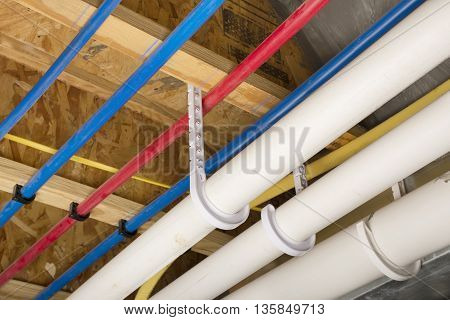 PEX and drain pipes attached to the basement ceiling of a home.