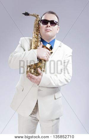 Male Saxophone Player Posing With Alto Saxo In White Suit and Sunglasses Against White Background. Vertical Image