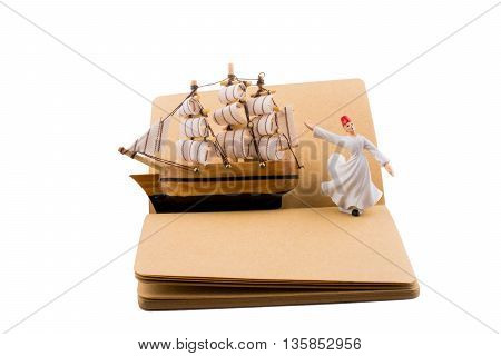 Sufi Dervish and a ship on a notebook on white background
