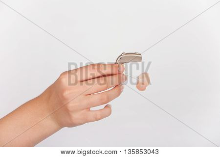 Audiologists hand holds a hearing aid with earmold. Studio isolated.