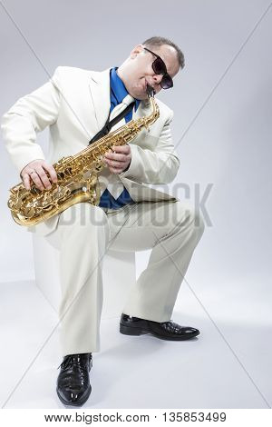 Music Concepts. Caucasian Mature Male Musician Playing Alto Saxophone and Wearing Sunglasses. Posing in White suit Against White. Vertical Image Composition