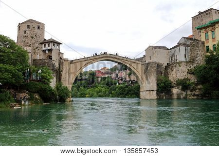 The old bridge that crosses river Neretva and connects the two parts of the city of Mostar in Bosnia and Herzegovina in a gloomy and rainy day