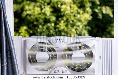 Two way window fan in home window with blurred out trees in background.