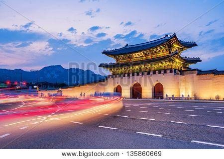 Traffic Blurs Past Gyeongbokgung Palace At Night In Seoul, South Korea.