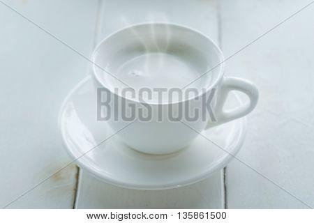 Hot milk in white mug on white table soft focus