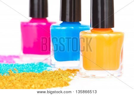 Nail polish and powdery eye shadow on a white background