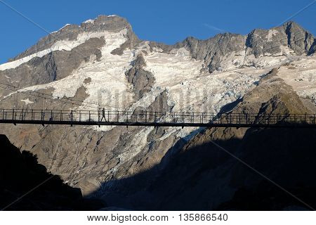 A Single Woman Hiker on a Bridge, Hooker Valley Track.  Mt Cook National Park, Southern Alps, New Zealand
