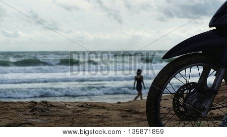 Silhouette of front wheel of motorcycle parked at beach in front of ocean, waves splashing on seashore. Silhouette of unidentifiable woman walking on the beach.