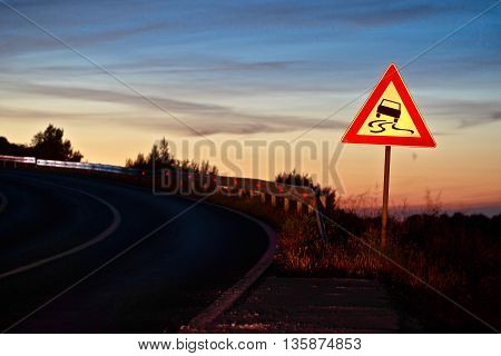 Curvy road sliding danger traffic sign at sunset next to road lane