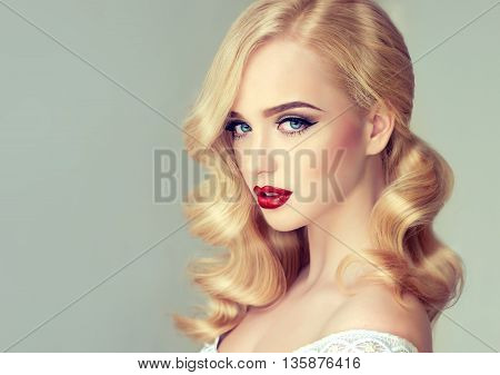 Beautiful blonde girl with bright makeup, with red lips and blue eyes. Woman with curly hair ,styling hairstyle