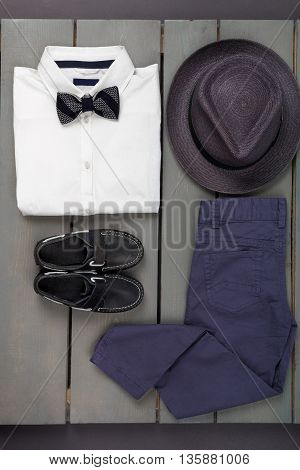 Men's outfit on wooden background. Kids fashion clothes. Grey fedora navy pant white shirt black bow tie and boat shoes for boy. Top view.