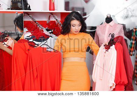 Young woman shopping in a clothing store. Woman shopping for dress in clothing retail store. Caucasian shopper girl choosing red dress in shop during sale. Woman shopping for dress. Fashion shopping