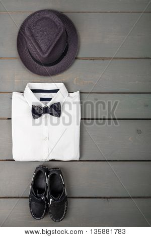 Men's outfit on wooden background. Kids fashion clothes. Grey fedora white shirt black bow tie and boat shoes for boy. Top view. Copy space. Frame