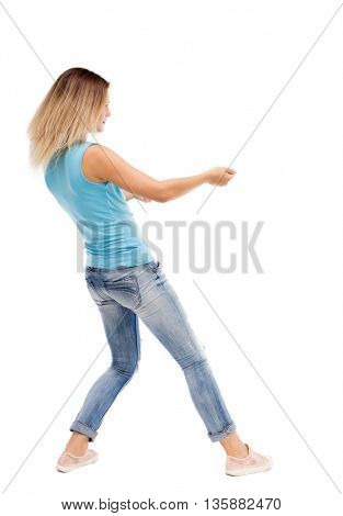 back view of standing girl pulling a rope from the top or cling to something. girl  watching.  Isolated over white background. The girl in jeans and a blue shirt pulling the rope on the left.