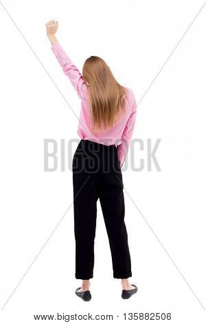 Back view business woman. Raised his fist up in victory sign. Raised his fist up in victory sign. Rear view people collection.  girl office worker in black trousers held up her hand in victory sign