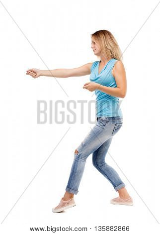 back view of standing girl pulling a rope from the top or cling to something.  Rear view people collection.  backside view of person.  The girl in jeans and a blue shirt pulling the rope on the right.
