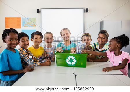 Portrait of pupils recycling in classroom