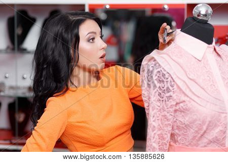 Young woman shopper astonished price on the dress. Young woman shopping in a clothing store. Caucasian shopper girl choosing pink dress in shop during sale. Woman shopping for dress. Fashion shopping