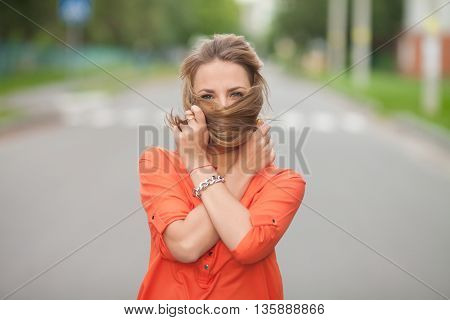 Surprised woman, delight, joy. Portrait of a woman on the street. Joy, positive emotions. Happy face. Open mouth.  Green trees, summer, park