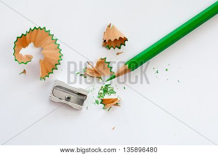 sharpener green wooden pencil and pencil shavings on white