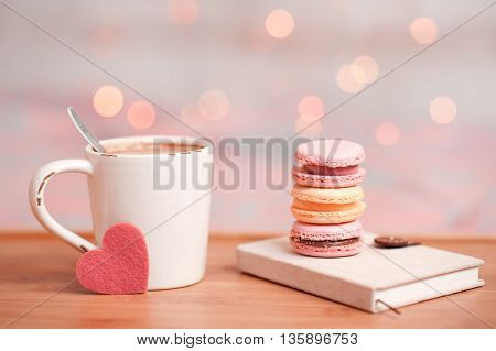 Colorful macaroons staying on book with cup of coffee and little heart over christmas lights. Good morning. Selective focus.